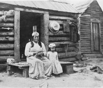 Native American woman and child in front of log cabin